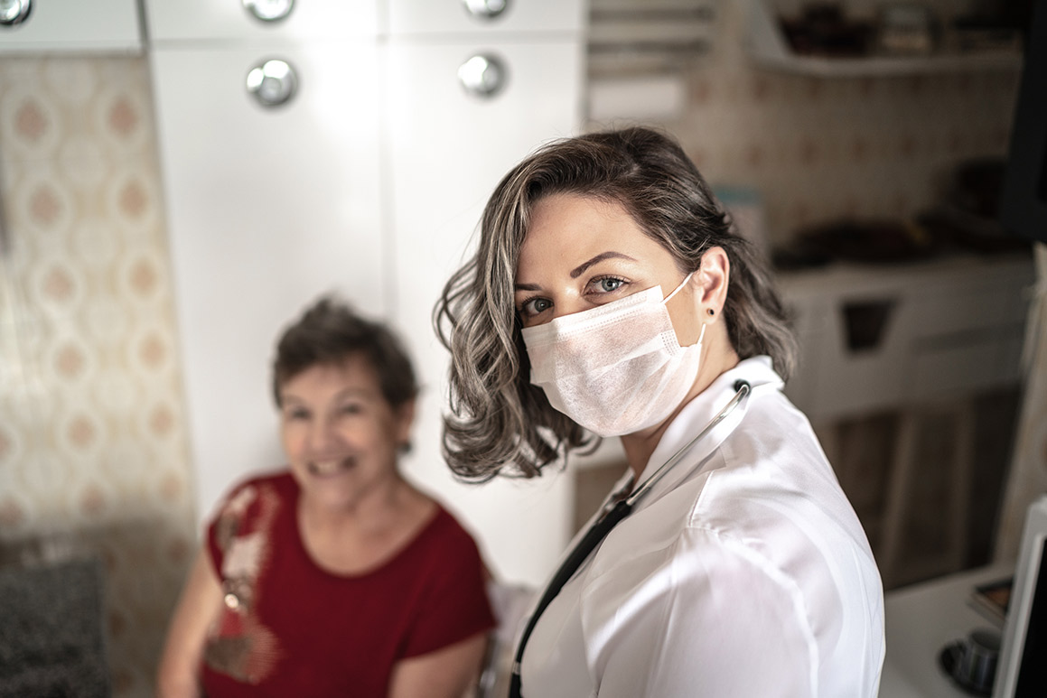 Assisted living nurse wears a mask and tends to a patient